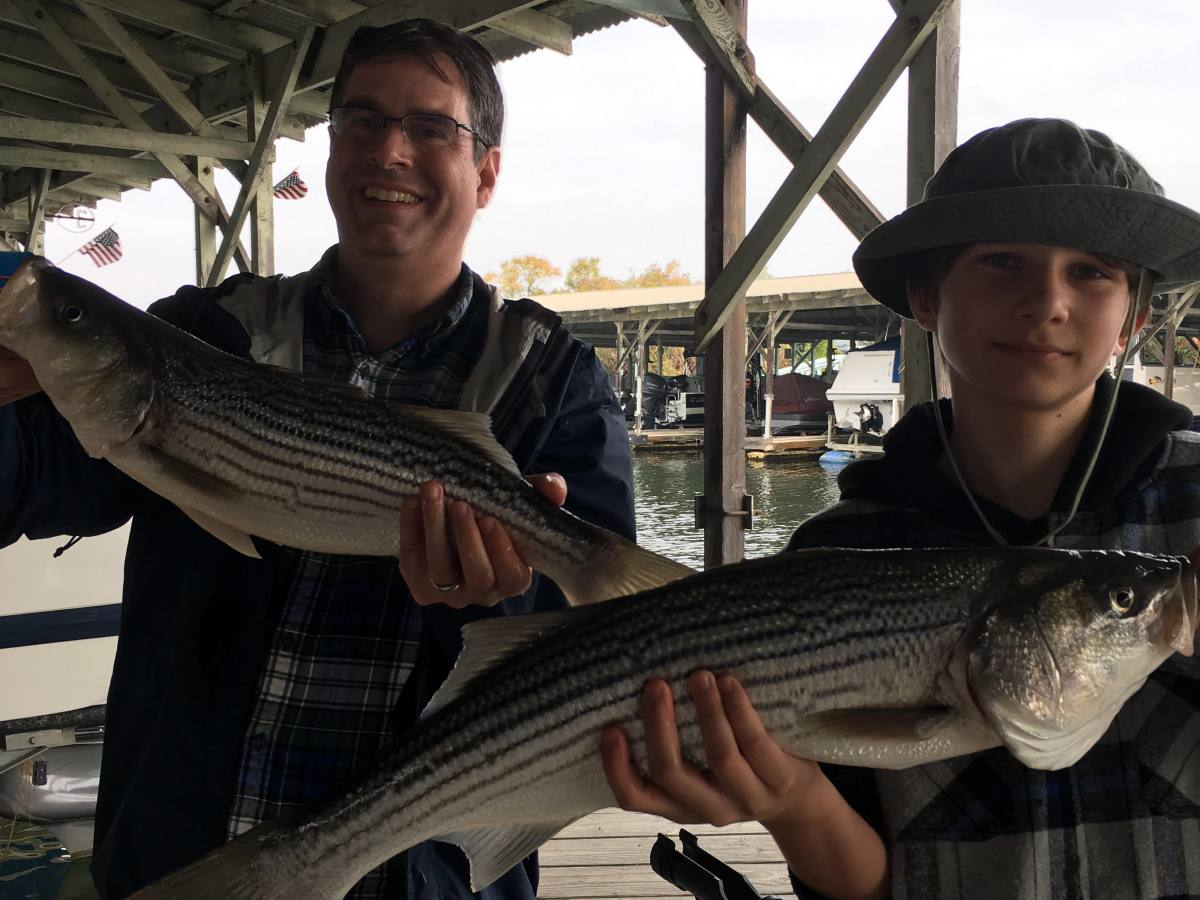 Father and Son holding striper fish